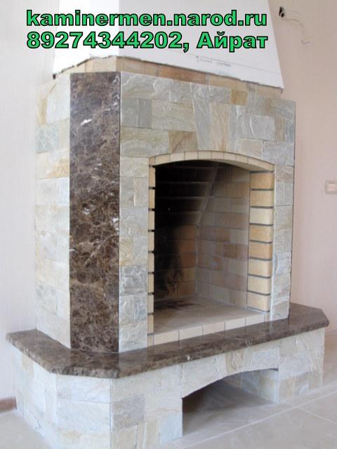 Камин с облицовкой мрамором и природным камнем.